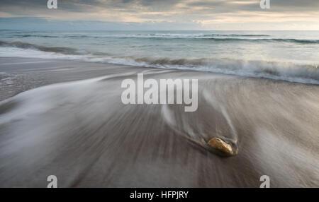 Kiesel am Strand auf einem schwarzen Sand und fließt Meerwasser schöne Texturen erstellen. Langzeitbelichtung Bild. - Stockfoto