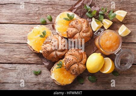 Süße Brötchen mit Zitrone Marmelade und Butter auf dem Tisch. Horizontale Ansicht von oben - Stockfoto