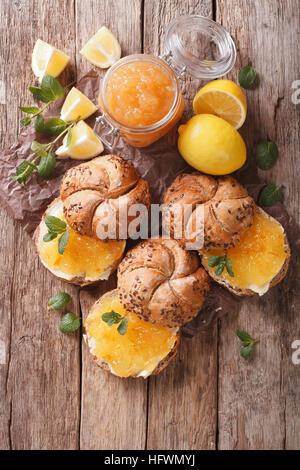 Süße Brötchen mit Zitrone Marmelade und Butter auf dem Tisch. vertikale Ansicht von oben - Stockfoto