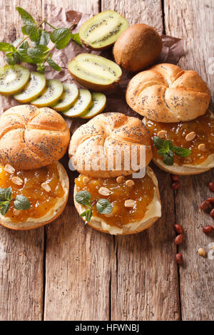 Süße Brötchen mit Butter, Kiwi Marmelade und Erdnuss close-up auf dem Tisch. Vertikal - Stockfoto