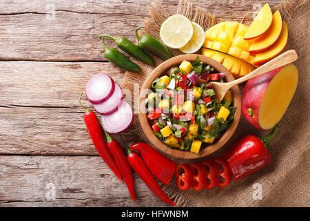 Mexikanische Salsa mit Mango, Koriander, Zwiebeln und Peperoni hautnah in einer Holzschale und Zutaten auf den Tisch. - Stockfoto
