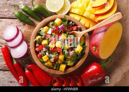 Salsa mit Mango, Koriander, Zwiebeln und Paprika in eine Schüssel geben und die Zutaten auf dem Tisch hautnah. Horizontale - Stockfoto