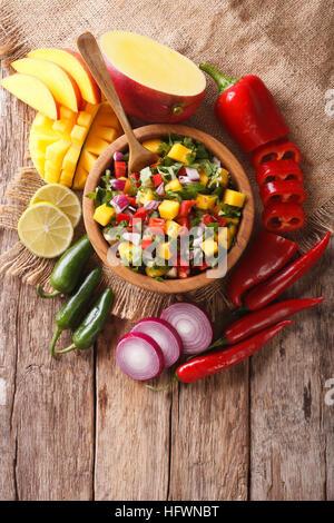 Mexikanisches Essen: Salsa mit Mango, Koriander, Zwiebeln und Paprika hautnah in eine Schüssel geben und die Zutaten - Stockfoto