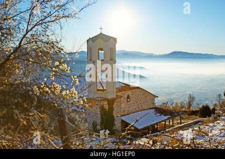 Die alte orthodoxe Kirche mit Friedhof, umgeben von Wintergarten mit nebligen Tal von Kastoria auf dem Hintergrund, - Stockfoto