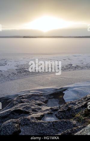 Schneebedeckten Felsen an einem zugefrorenen und verschneiten See in Finnland am Morgen im Winter. - Stockfoto