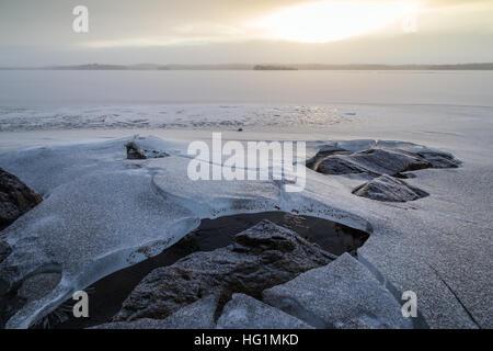 Fels unter gestoßenem Eis auf einem gefrorenen See in Finnland am Morgen im Winter. - Stockfoto