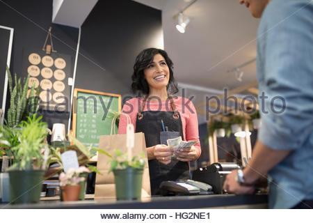Weibliche Shop-Betreiber zählen Bargeld helfen Kunden bei Pflanze Ladentheke - Stockfoto