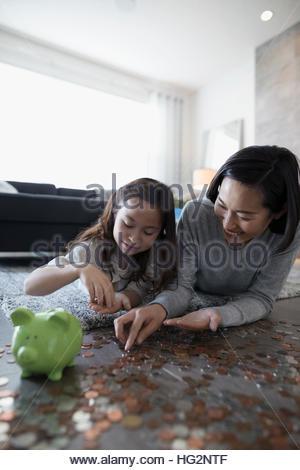 Mutter und Tochter zu zählen und Hinterlegung Münzen ins Sparschwein am Boden des Wohnzimmers - Stockfoto