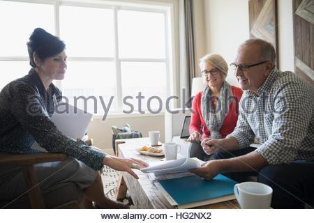 Finanzberater diskutieren Papierkram Treffen mit leitenden paar im Wohnzimmer - Stockfoto