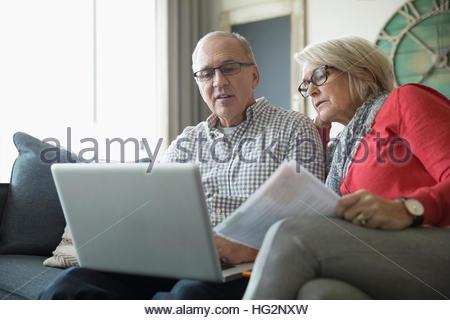 Älteres Paar mit Papierkram mit Laptop auf dem Sofa im Wohnzimmer - Stockfoto