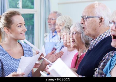 Gruppe von Senioren mit Lehrer singen im Chor zusammen - Stockfoto