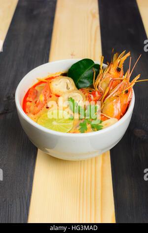 Tom Yum Soup oder Fluss Garnelen scharf saure Suppe (Tom Yum Goong) auf Holztisch, thailändische Spezialitäten - Stockfoto