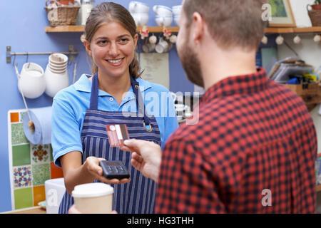 Kunden zahlen für Kaffee zum Mitnehmen mit kontaktlosen Terminal - Stockfoto
