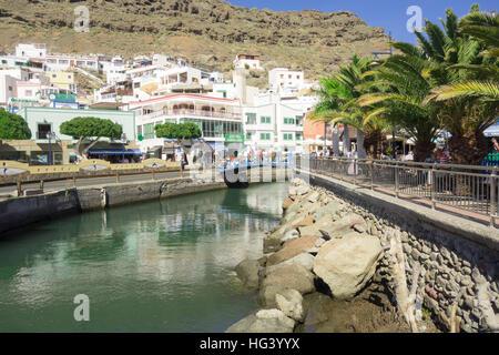 Ein kleiner Fluss in einer Ferienanlage namens Puerto de Mogan auf Gran Canaria mit Puerto de Mogán Brücke im Hintergrund. - Stockfoto
