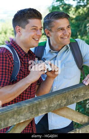 Vater mit erwachsenen Sohn auf Spaziergang In der Natur mit dem Fernglas - Stockfoto
