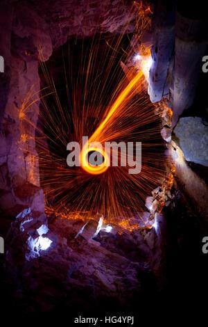 Stahl Wolle spinnen Funken in einer unterirdischen Höhle mit Steinen. - Stockfoto
