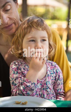 zwei Jahre alte Mutter kleine Kind essen Oliven sitzen auf Frau Beine außen Restaurant - Stockfoto