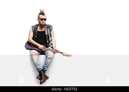 Junge punker mit einer e-Gitarre, sitzend auf einem Panel isoliert auf weißem Hintergrund - Stockfoto