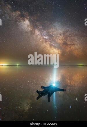 Mann auf See Elton in Russland unter der Milchstraße während scheint eine Taschenlampe oben liegend. - Stockfoto