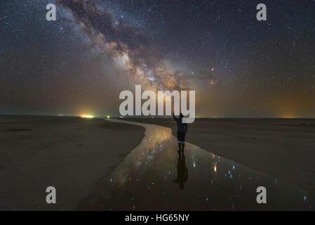 Ein Mann zu Fuß auf dem Salt River in der Nacht unter der Milchstraße, Russland. - Stockfoto