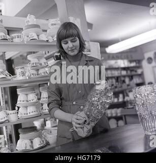 1960er-Jahren, historische, reinigt junge weibliche Verkäuferin die Glaswaren im Departement Geschirr. Stockfoto