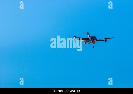 Kleine moderne Drohnen gegen blauen Himmel schweben - Stockfoto