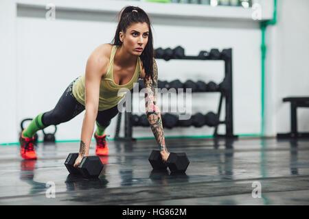 Zuversichtlich Sportler tun Hantel Liegestützen im Fitness-Studio - Stockfoto