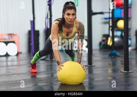 Athlet doing Push-ups mit Medizinball im Fitness-Studio - Stockfoto