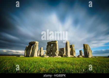 Stonehenge an einem sonnigen und windigen Wintertag. Alte Ruinen in Wiltshire, England, keine Menschen oder Touristen. Grünes Gras im Vordergrund, bewegte Wolken.