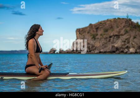 Frau sitzt auf Paddleboard im Meer gegen Himmel - Stockfoto