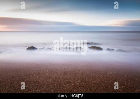Felsen am Strand wird durch die Flut während des Sonnenuntergangs getaucht - Stockfoto