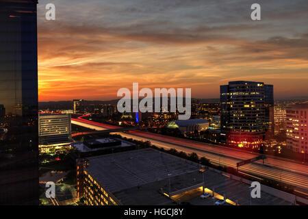 Sonnenaufgang über leichte Wanderwege und die Lichter der Stadt auf einer Autobahn in Irvine, Kalifornien, USA. - Stockfoto