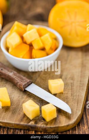 Kaki Früchte auf einem Vintage-Hintergrund als detaillierte Nahaufnahme (Tiefenschärfe) - Stockfoto