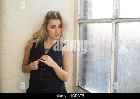 Schöne blonde Frau aus dem Fenster - Stockfoto