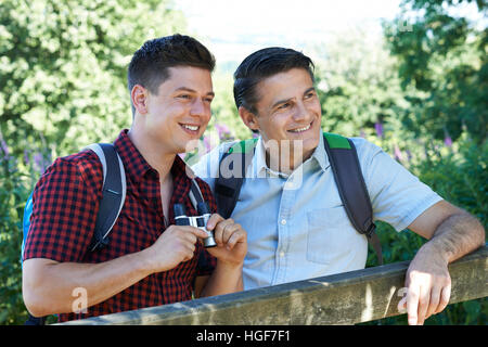 Vater und erwachsener Sohn Wandern In Natur, Blick durch ein Fernglas - Stockfoto