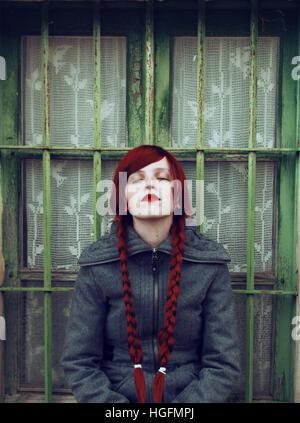 Junge rothaarige Frau, mit zwei langen Zöpfen, sitzen in der Nähe von einem alten Fenster - Stockfoto