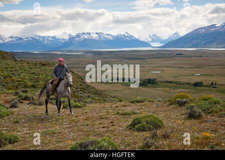 Gaucho auf dem Pferderücken bei Estancia Alta Vista mit der Anden und Gletscher Perito Moreno, El Calafate in Patagonien, Argentinien