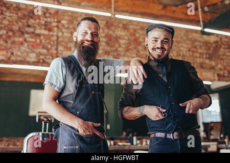 Porträt von professionellen Friseur mit seinem Klienten stehen im Friseurladen. Friseur mit zufriedenen Kunden im - Stockfoto