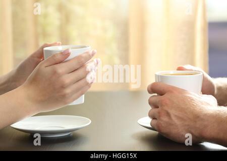 Nahaufnahme der Seitenansicht eines Paares oder Freunde reden mit Händen mit Kaffeetassen auf dem Tisch ein Fenster - Stockfoto