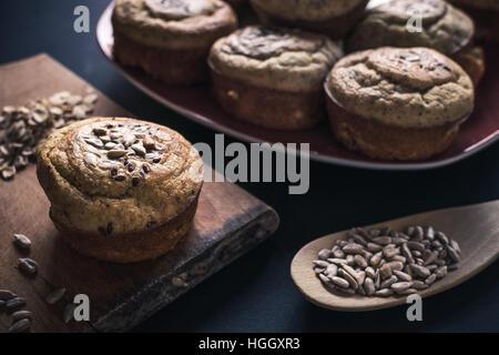 Teller mit Muffins und gemischte Samen auf Tisch Stockfoto