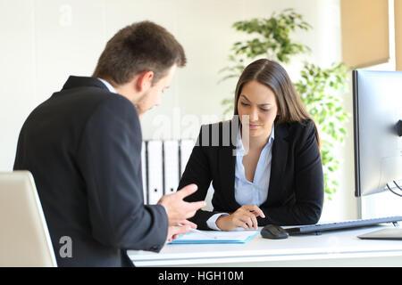 Schlechter Geschäftsmann versucht, an einen Verdächtigen Kunden während einer schwierigen Verhandlung in einem Desktop - Stockfoto