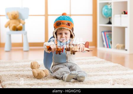 Glückliches Kind Junge spielt mit Spielzeugflugzeug zu Hause in seinem Zimmer - Stockfoto