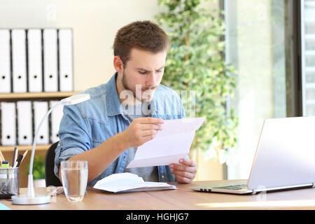 Ernsthafte Unternehmer arbeiten und liest einen Brief in einem Desktop am Arbeitsplatz - Stockfoto