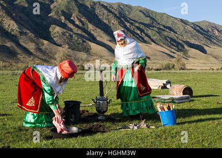 Kasachische Frauen in Trachten kochen Fleisch unter freiem Himmel, im Dorf bleiben, Kasachstan - Stockfoto