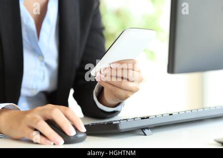 Nahaufnahme einer Geschäftsfrau Hände mit einem Desktop-Computer-Maus und Smartphone online im Büro - Stockfoto