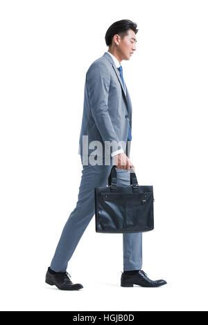 Müde junger Geschäftsmann mit Aktenkoffer - Stockfoto