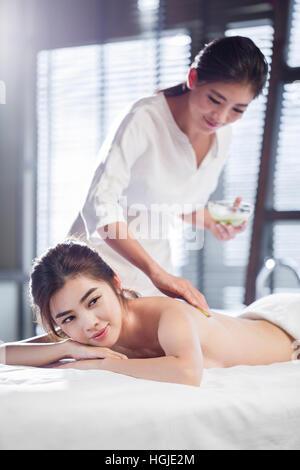 Junge Frau empfangen Rückenmassage im Wellnesscenter - Stockfoto