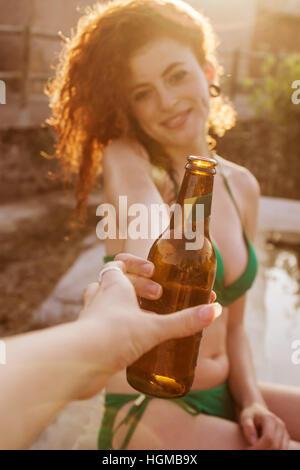 Junge rothaarige Frau an ein Sommerfest mit einer Bierflasche - Stockfoto