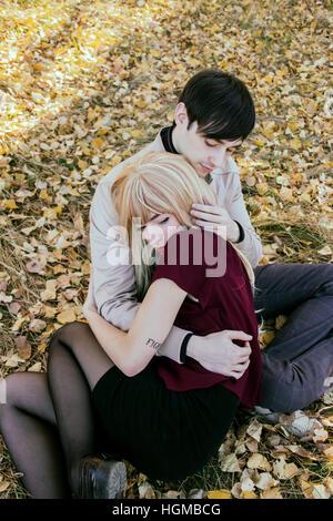 Junges Paar umarmen einander in einem Park im Herbst - Stockfoto