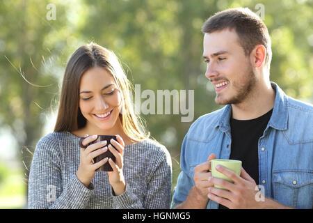 Vorderansicht eines Paares flirten und reden in einem Park mit einem grünen Hintergrund bei Sonnenuntergang - Stockfoto